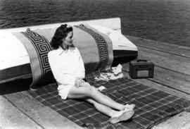 [Woman on resort wharf sunbathing]