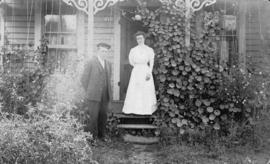 Mr. and Mrs. Tyler [on front porch of house]