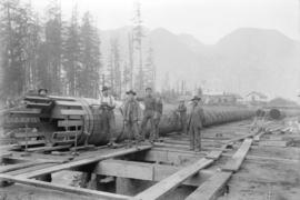 [Group of men standing next to partially constructed wooden penstock for Buntzen Lake Power Plant...