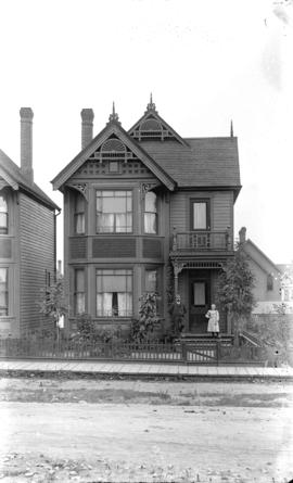 [Man and girl standing on front steps of residence at 651 Richards Street]
