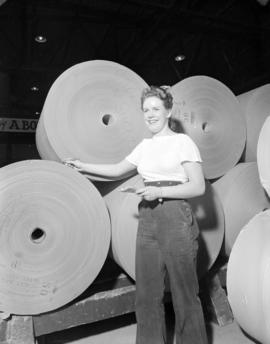 [Woman standing beside paper] rolls [at] Pacific Mills