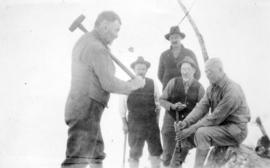 [Group photograph of men in snow, showing man with a sledgehammer preparing to hit stake held by ...