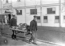 29th Battalion and Yukon Detachment [two soldiers carrying rack piled with bread]