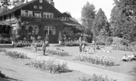 [People gathered on lawn by flower beds in front of the Stanley Park Pavilion]