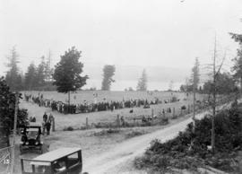 [View of crowd lining a field to watch a sporting activity]