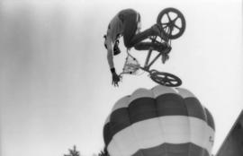 Man performing bike trick with hot air balloon in background