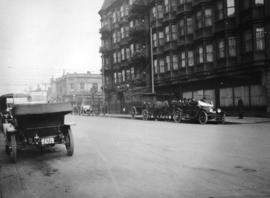 [Taxicabs and a horse-drawn carriage parked outside a building]