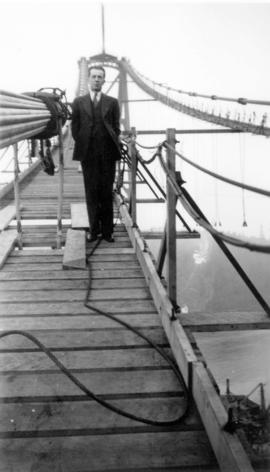 [An unidentified man standing on the Lions Gate (First Narrows) Bridge during construction]