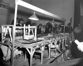 Spectators viewing working model of sawmill at P.N.E.