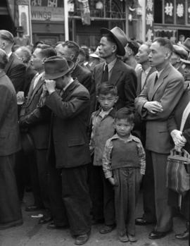 [Two Chinese boys standing in a crowd watching VJ Day celebrations in Chinatown]