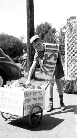 Young boy with garbage cart at a Kitsilano parade