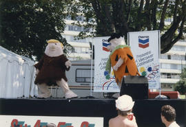 Barney Rubble and Fred Flintstone mascots on Chevron stage at Centennial event