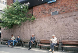 Men sitting on benches against mural in Montreal Chinatown