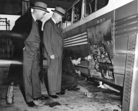 [E.W. Arnott and George Miller watch a mechanic inspect a new B.C. Electric Railway bus]
