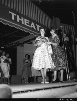 Carol Lucas, winner of Miss P.N.E. 1957, receives sash from the previous year's winner, Joan...