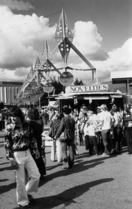 Crowd around novelties booth on P.N.E. grounds, with Pacific Coliseum in background