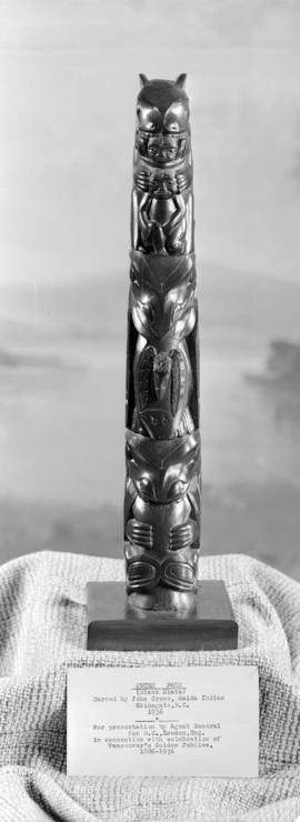 Front view of (black slate) totem pole presented to Sir Percy Vincent in connection with the cele...