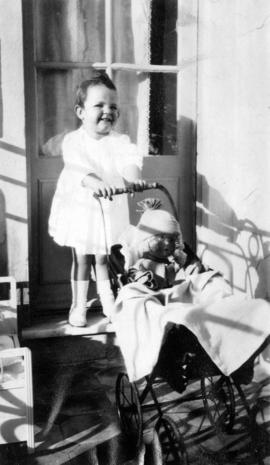 [Mary Louise Taylor pushing doll in buggy]