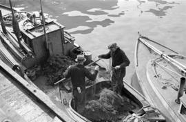 [Two men repairing nets on a boat]